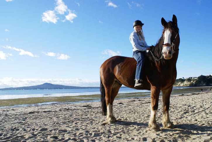 Tane and Genna on St Heliers Bay beach with Auckland's iconic Rangitoto Island in the background